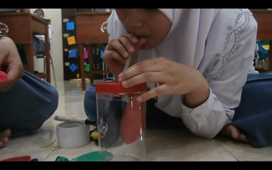 Gambar di atas adalah kutipan film dokumenter praktikum biologi  oleh murid-murid SMA A Wahid Hasyim. Film tersebut memperlihatkan praktikum biologi mengenai proses respirasi atau pernapasan manusia dengan menggunakan bahan-bahan sederhana seperti balon, pipa, dan toples plastik makanan. Sumber gambar: www.ma-biology.blogspot.com