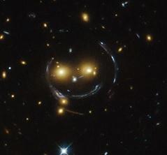 Senyum dari langit yang merupakan salahsatu fenomena lensa gravitasi. Gambar dari: NASA & ESA.